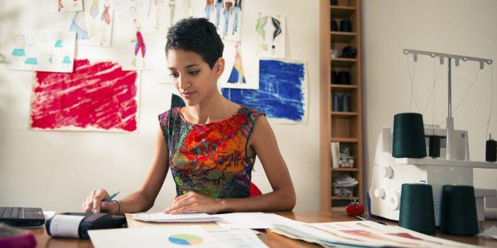 Ung latinamerikansk kvinna som driver eget företag. Hon gör en budget i sin studio med hjälp av sina fakturor och försäljningsdiagram.