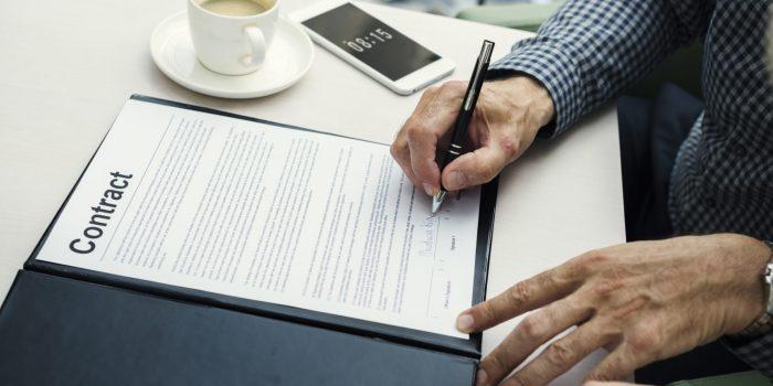 En man som signerar ett avtal om personlig borgen för ett företagslån till sitt bolag.