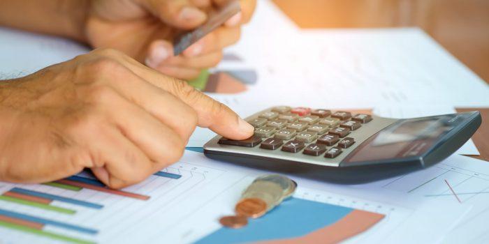 En man som jämför ränta och avgifter på olika företagslån med hjälp av miniräknare.