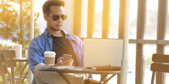 En nybliven näringsidkare sitter på ett café och arbetar med sitt företag på sin laptop.